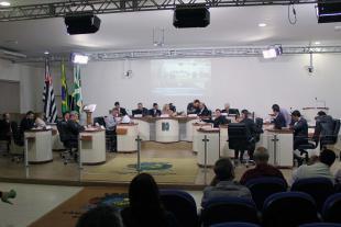 #PraCegoVer: Foto mostra visão geral do plenário com parte do público presente assistindo à sessão. No centro, os vereadores estão sentados nos seus lugares.