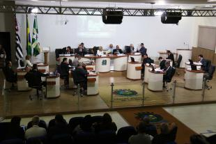 #PraCegoVer Foto mostra o plenário da Câmara visto de cima, com todos os vereadores sentados nos seus lugares e parte do público que acompanha a sessão