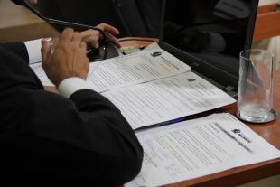 #PraCegoVer: Foto mostra braço de vereador sobre a mesa, onde também há documentos e um copo de água vazio.