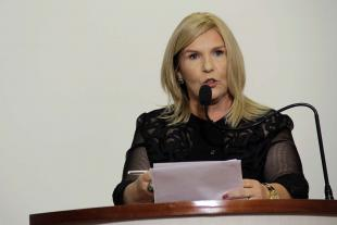 #PraCegoVer: Foto da presidente da Câmara, vereadora Dalva Berto, segurando um documento e discursando na tribuna para os demais vereadores e para o público.