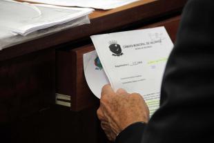 #PraCegoVer: Foto mostra vereador segurando um documento, sentado em sua cadeira.