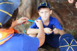 #PraCegoVer - Um menino vestido com roupas de escoteiro mostra ao outro como fazer um nó com um cordão azul