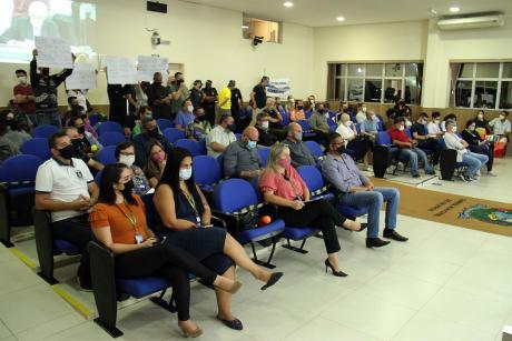 #PraCegoVer: Foto mostra público acompanhando a sessão. No fundo do plenário, há pessoas segurando cartazes contra o projeto de lei.